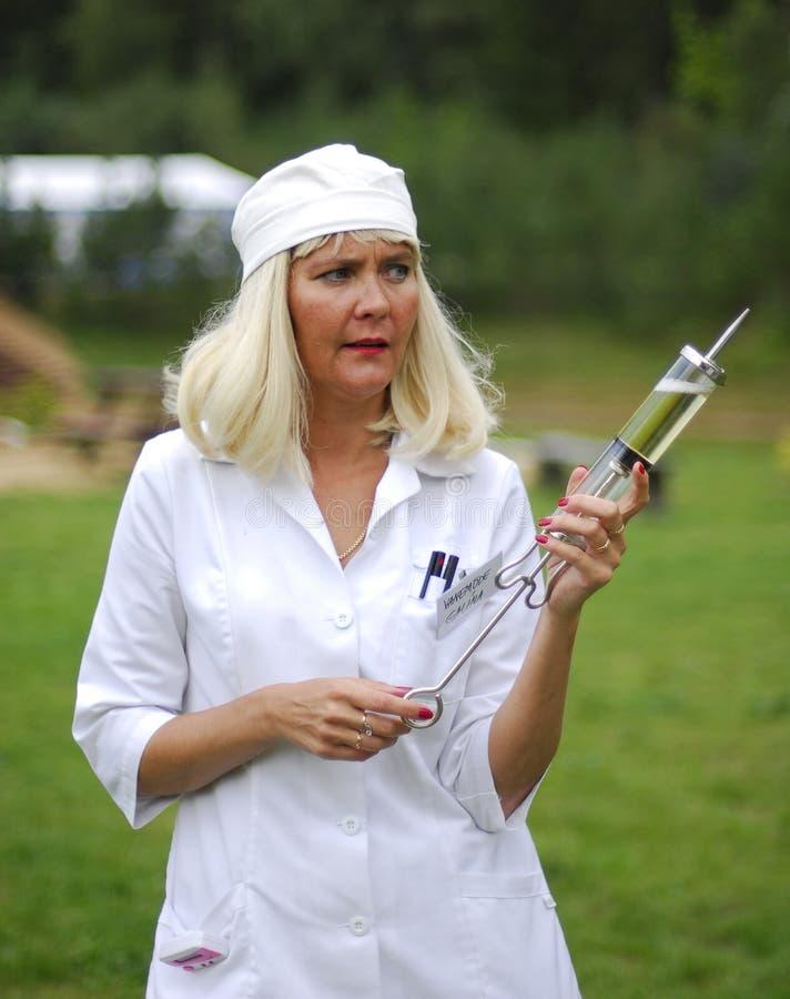 Krankenschwester mit einer gigantischen Spritze stockbilder