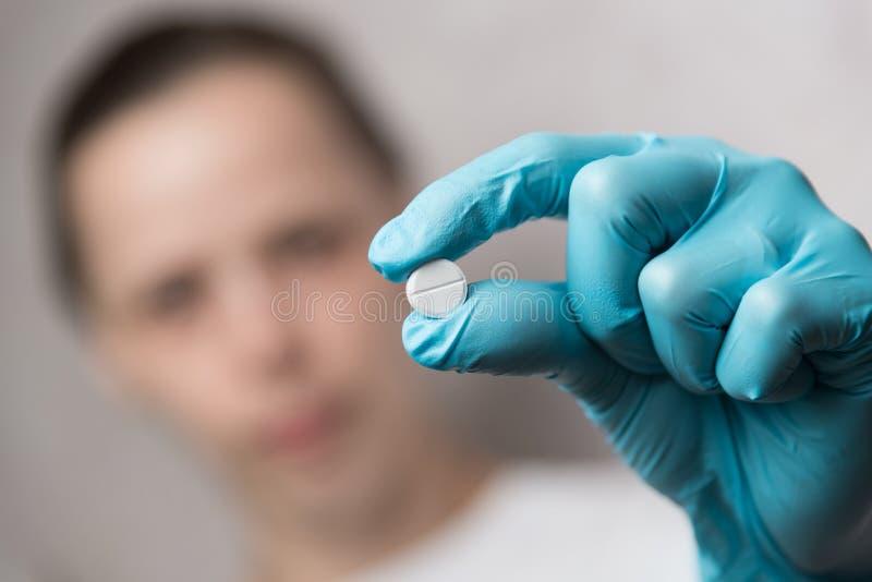 Krankenschwester mit Handschuhen mit einer Pille lizenzfreies stockbild