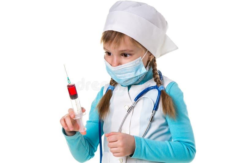 Krankenschwester mit medizinischer Gesichtsmaske und eine Spritze mit einer roten Substanz, Landschaft lizenzfreie stockbilder