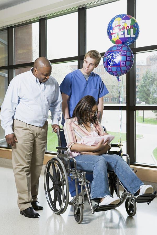 Krankenschwester mit neuen Eltern und Baby stockbild