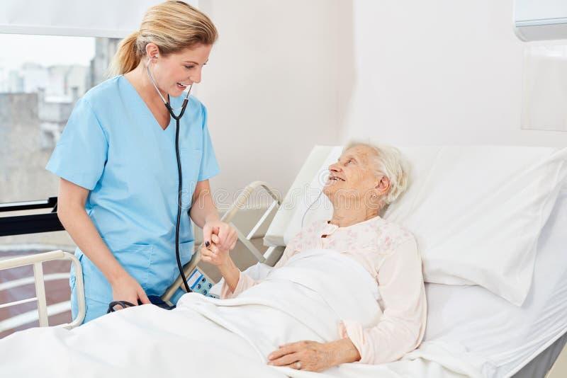 Krankenschwester mit Stethoskop am Kopfende stockbild