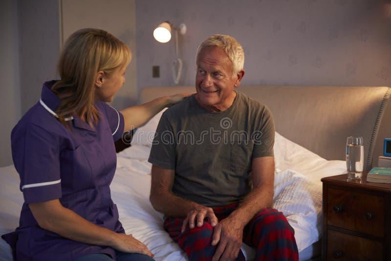 Krankenschwester-Talking With Senior-Mann im Schlafzimmer auf Hausbesuch stockbilder