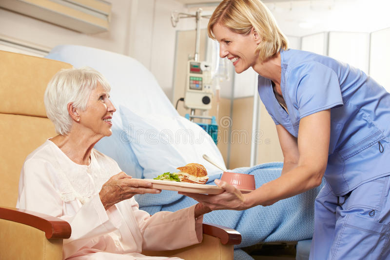 Krankenschwester-Umhüllungs-Mahlzeit zum älteren weiblichen Patienten, der im Stuhl sitzt stockfotos