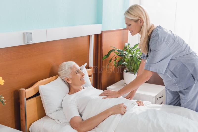 Krankenschwester und ältere Frau sich in der Krankenpflege lächeln lizenzfreies stockbild