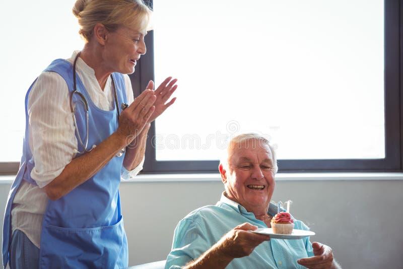 Krankenschwester und älterer Mann, die Geburtstag mit Muffin feiern lizenzfreie stockbilder