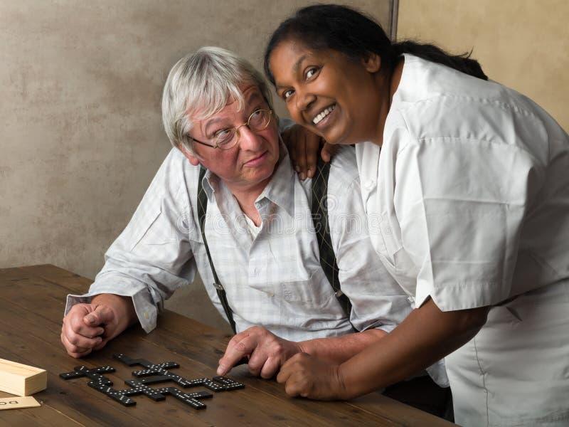 Krankenschwester und älterer spielender Domino lizenzfreies stockfoto