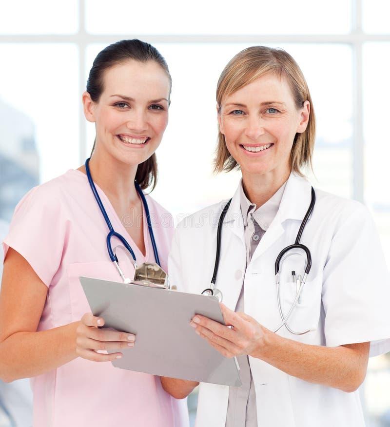 Krankenschwester und Doktor, die an der Kamera lächeln lizenzfreie stockbilder