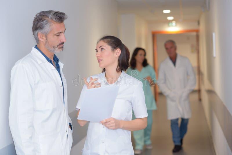 Krankenschwester und Doktor, die im Krankenhauskorridor sprechen lizenzfreies stockfoto