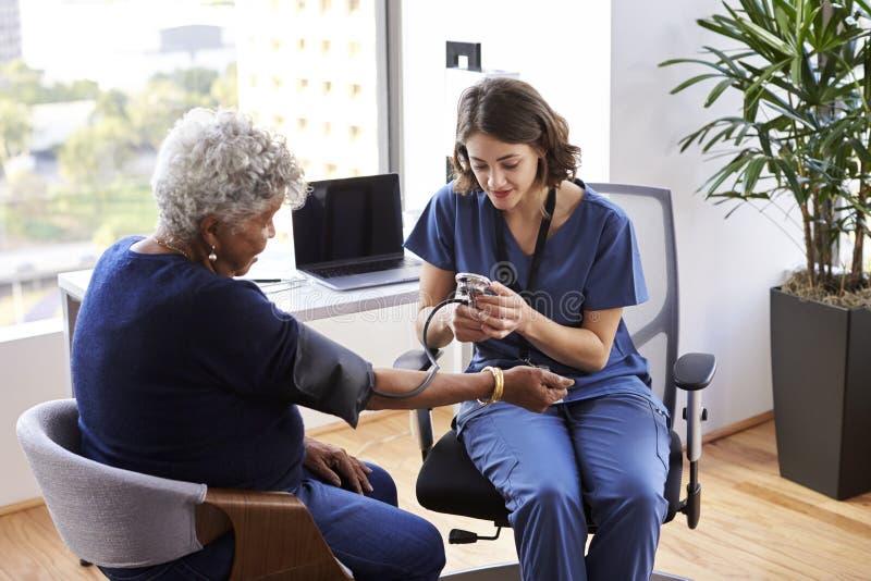 Krankenschwester-Wearing Scrubs In-Büro, das älteren Patientinnen-Blutdruck überprüft lizenzfreie stockfotografie