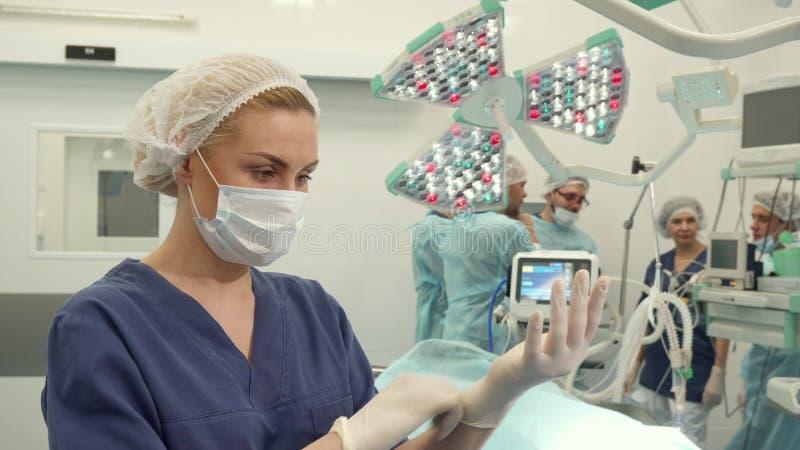 Krankenschwester zieht Handschuhe auf ihre Hände über lizenzfreie stockfotografie