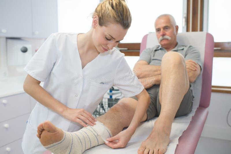 Krankenschwesterschiene warf auf Beinpatienten im Krankenhaus lizenzfreies stockbild