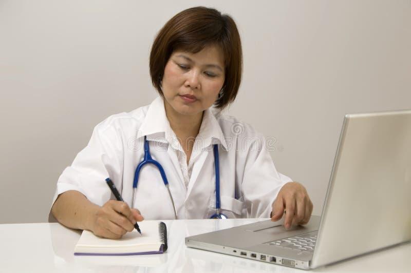 Krankenschwestersitzen und -schreiben lizenzfreies stockbild