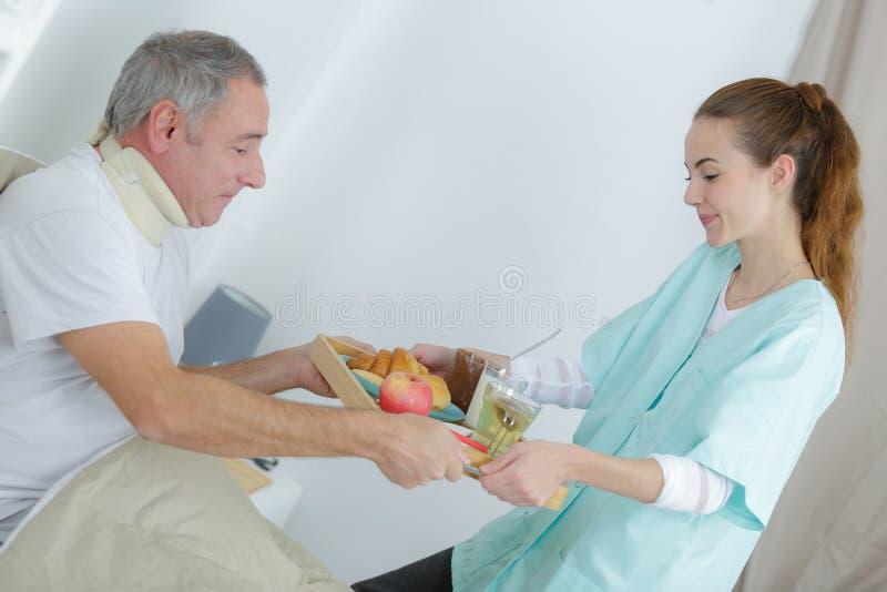 Krankenschwesterumhüllungsfrühstück zum älteren Mann zu Hause lizenzfreie stockbilder