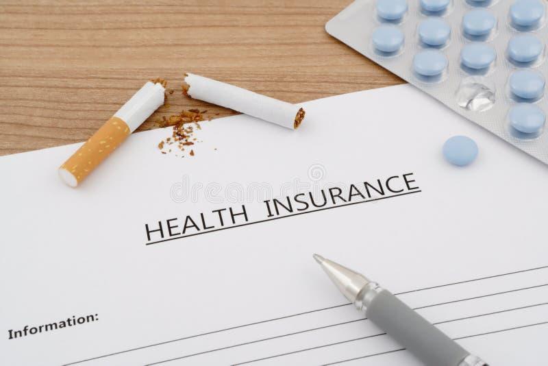Krankenversicherungsdokument mit Pillen und defekter Zigarette lizenzfreie stockbilder