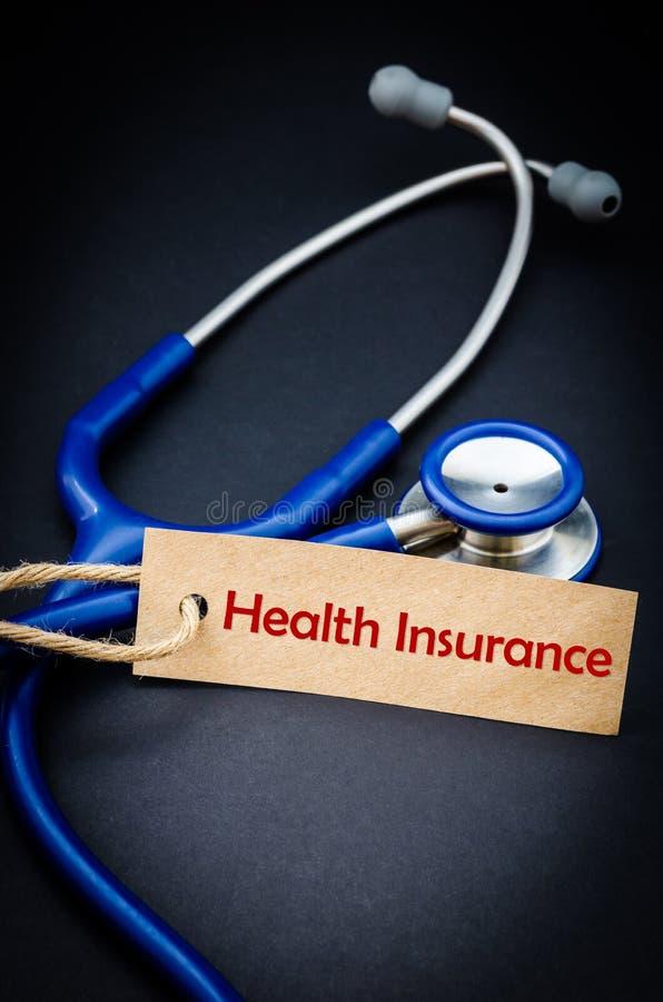 Krankenversicherungswort im Papiertag mit Stethoskop lizenzfreies stockbild