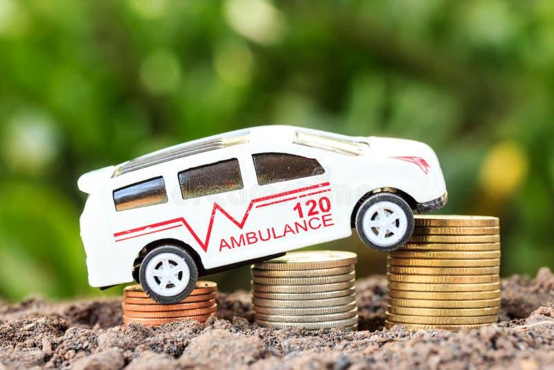 Krankenwagen auf Münze auf hölzernem Hintergrund stockbild