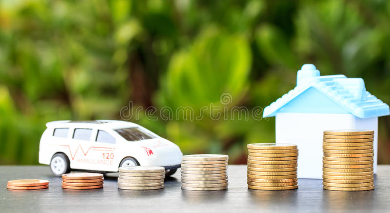 Krankenwagen und Haus auf Münze auf Hintergrund lizenzfreies stockbild
