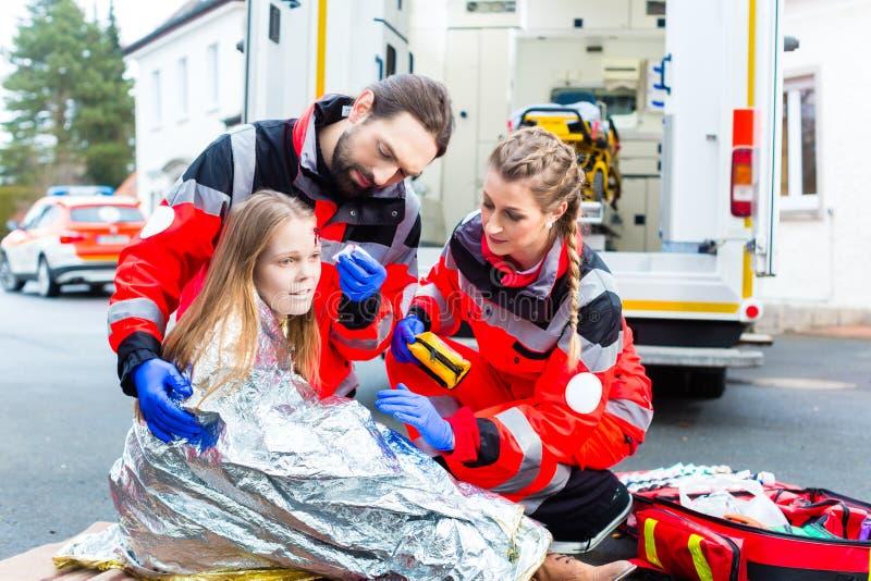 Krankenwagendoktor, welche verletzter Frau hilft lizenzfreie stockbilder