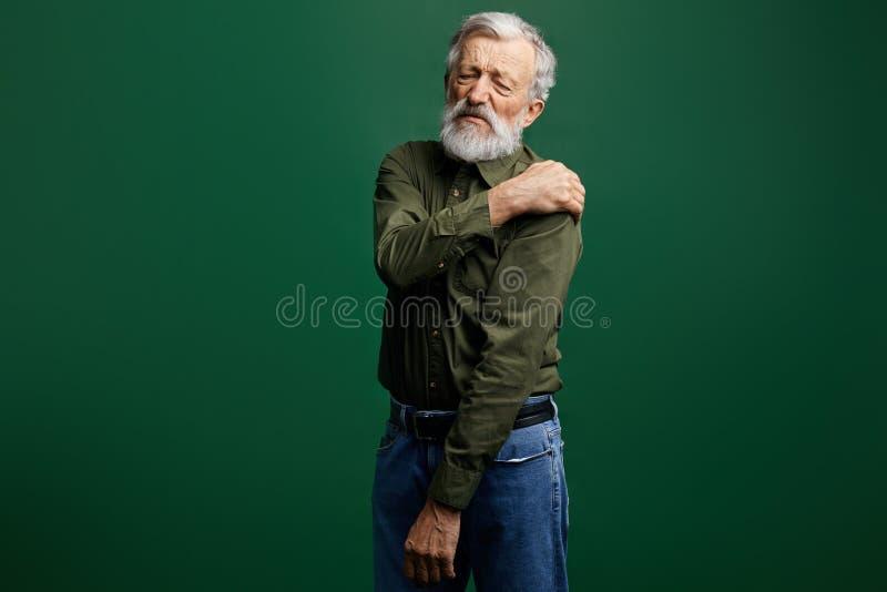 Kranker alter Mann hat die Schmerz im Hals, älterer Mann hat Schultergelenkluxation stockbild