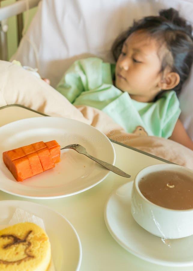 Kranker asiatischer Kinderkrankenhauspatient auf Bett mit Frühstücks-Mahlzeit-Menü stockfotografie