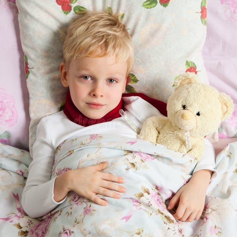 Kranker Junge ist im Bett lizenzfreie stockbilder