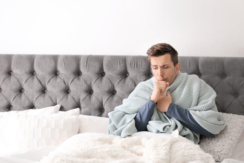 Kranker junger Mann mit dem Husten, der unter Kälte leidet stockfotografie