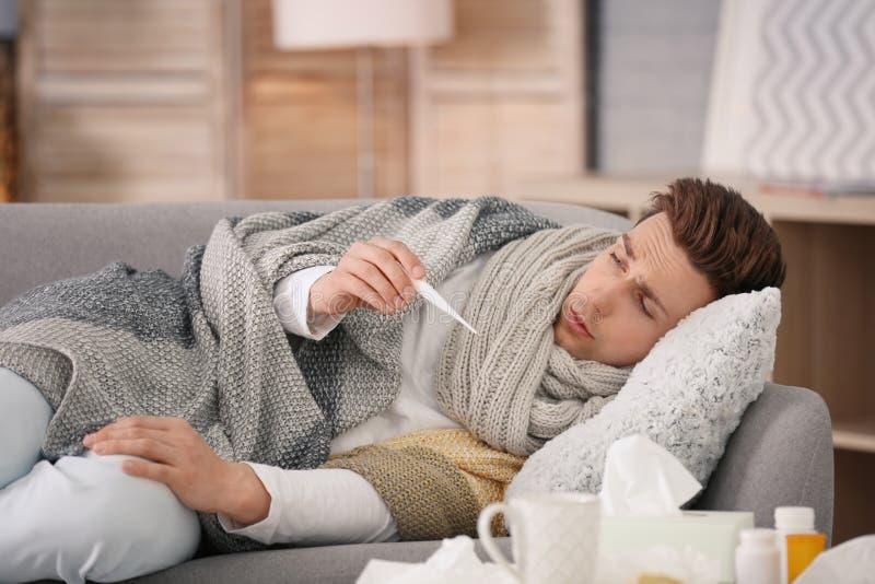 Kranker junger Mann mit dem Thermometer, der unter Kälte leidet lizenzfreie stockbilder