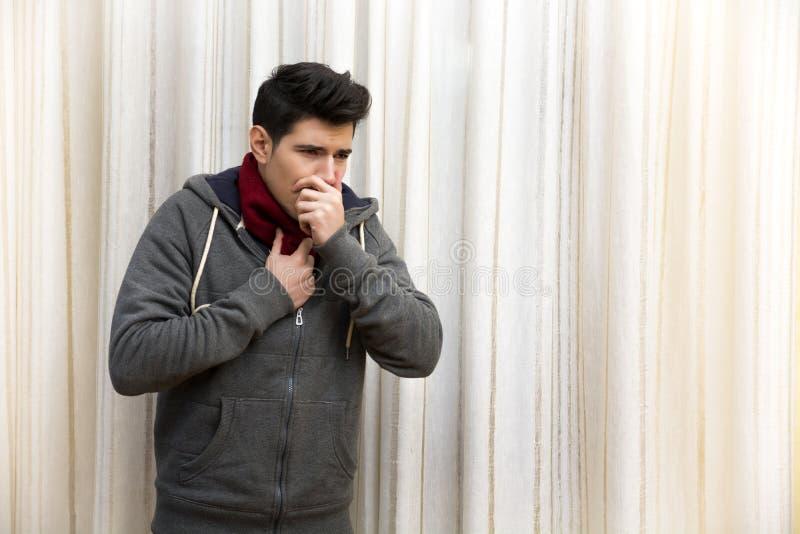 Kranker junger Mann mit der Grippe oder Kälte, hustend innen stockfotografie