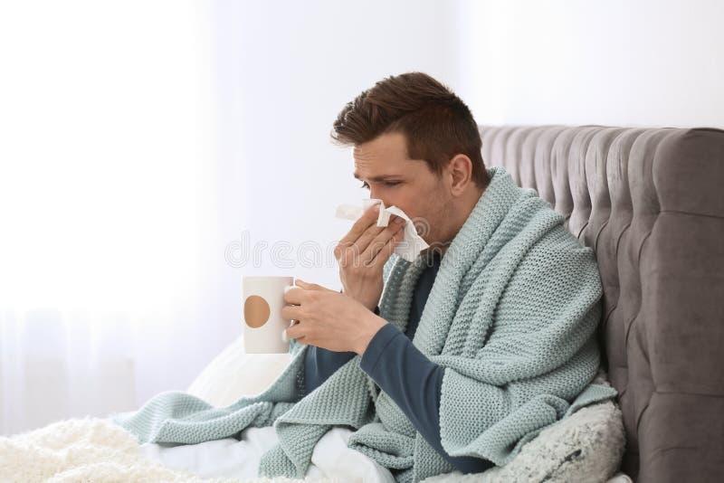 Kranker junger Mann mit Schale des heißen Getränks und des Gewebes lizenzfreies stockfoto