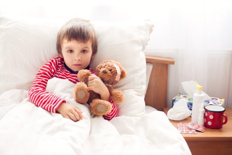 Kranker Kinderjunge, der im Bett mit einem Fieber, stehend liegt still stockfotos