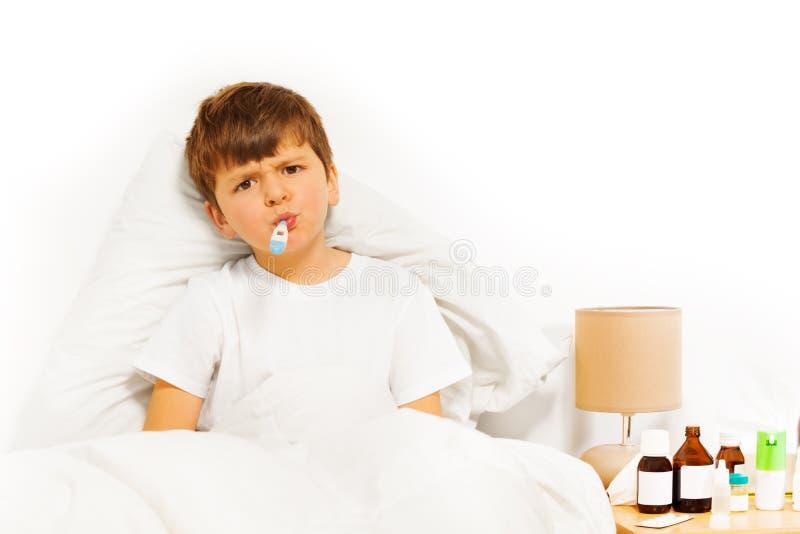 Kranker Kinderjunge, der im Bett sitzt und Temperatur nimmt lizenzfreies stockfoto