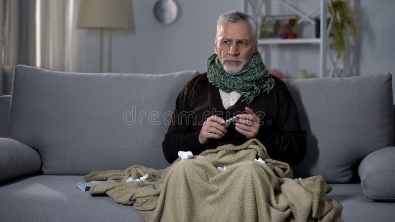 Kranker Mann bedeckt im Plaid, welches die Grippeentlastungspillen, Grippe behandelnd, Medizin hält lizenzfreie stockfotos