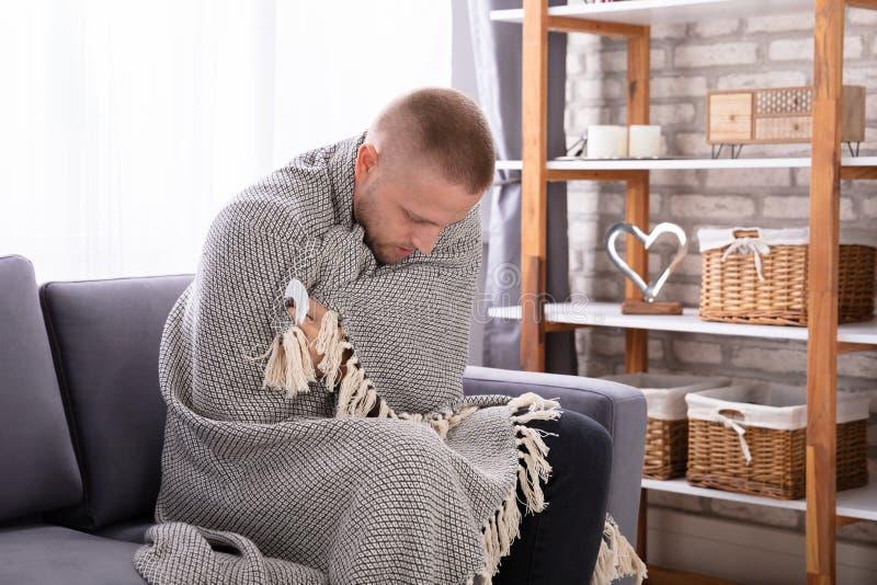 Kranker Mann bedeckt mit Decke stockbilder