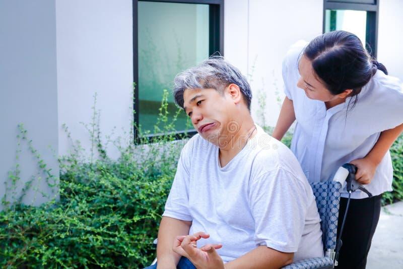 Kranker Mann, der auf einem Rollstuhl sitzt stockfotografie