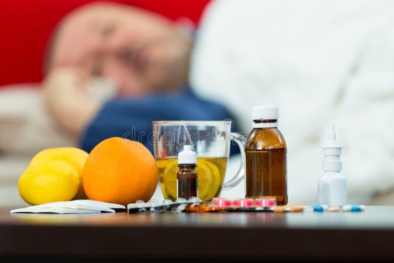 Kranker Mann im Bett mit Drogen und Frucht auf Tabelle lizenzfreie stockbilder