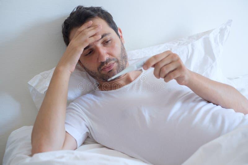 Kranker Mann in messender Temperatur des Betts und im schauen Thermometer lizenzfreie stockfotografie