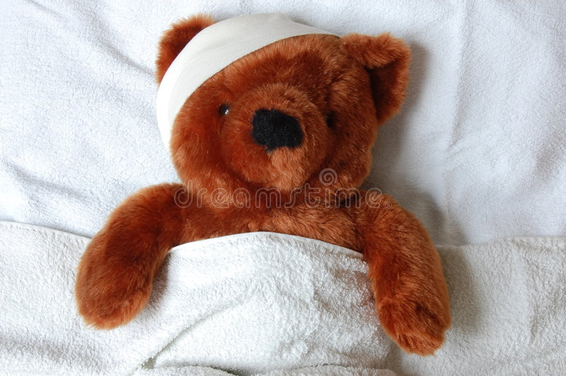 Kranker Teddybär mit Verletzung im Bett stockbilder