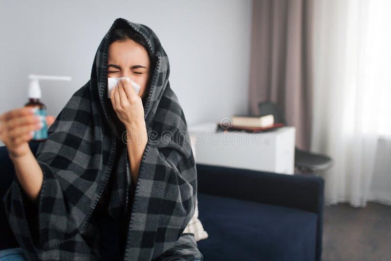 Kranker und unglücklicher Griffkehlspray der jungen Frau Sie bedeckt Nase mit weißem Gewebe Vorbildlicher Kranke Sie umfasst ihre stockbild