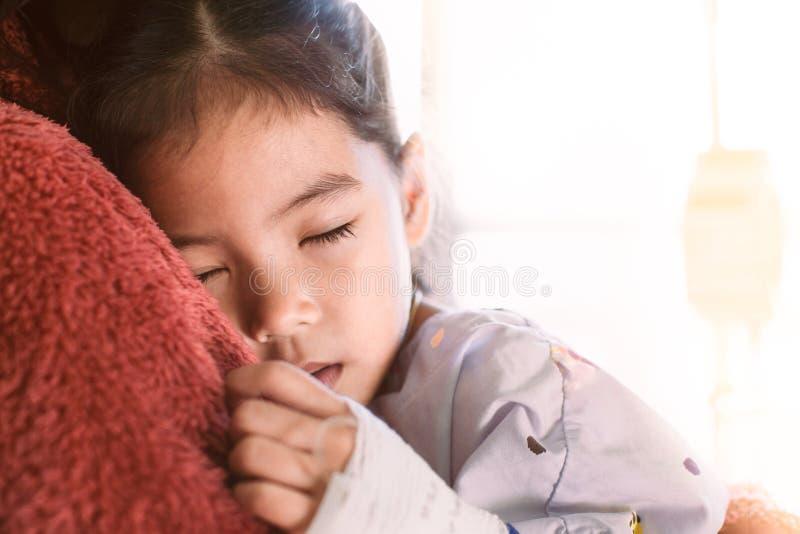 Krankes asiatisches Kindermädchen, das das Schlafen der Lösung IV haben stockfotografie