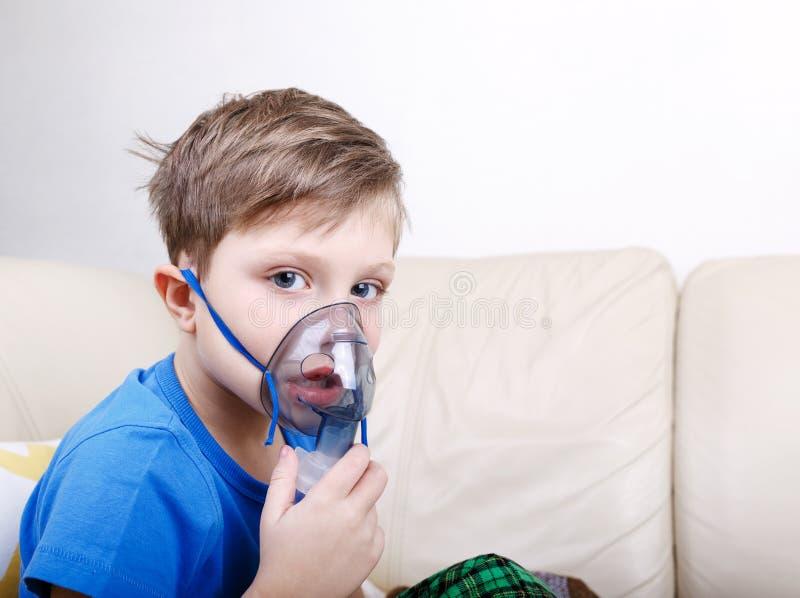 Krankes chid mit dem pädiatrischen Zerstäuber, der Kamera betrachtet stockbilder