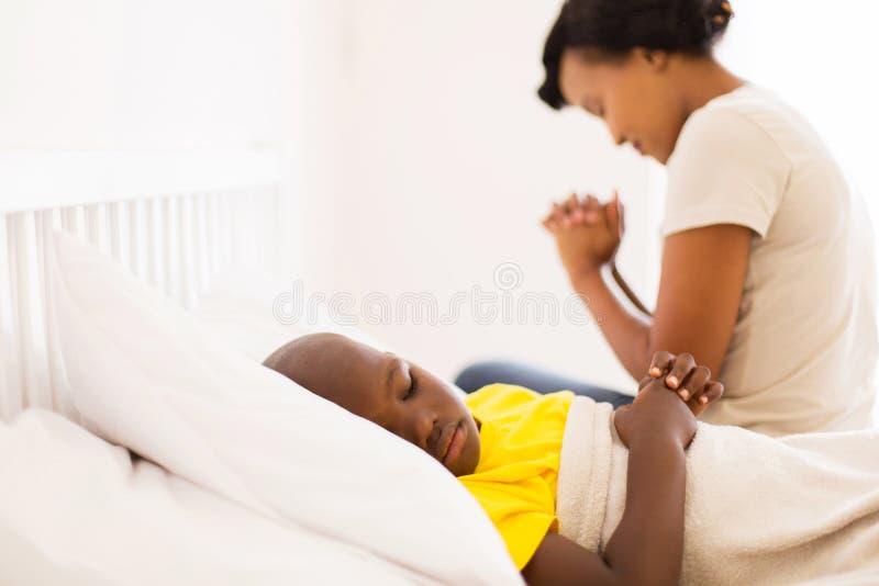 krankes Jungenmutterbeten lizenzfreie stockfotografie