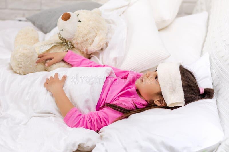 Krankes kaltes kleines Kinderm?dchen liegt im Bett lizenzfreies stockfoto
