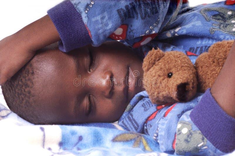 Krankes Kind, das mit seinem Teddybären schläft lizenzfreies stockbild