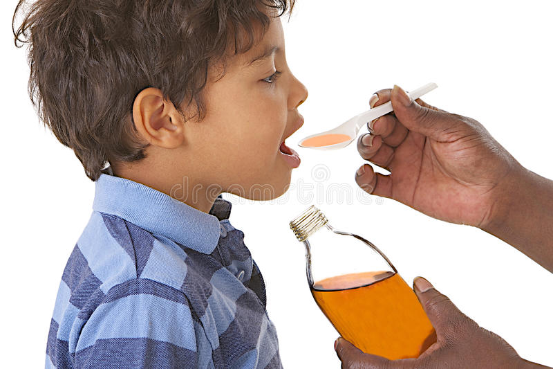 Krankes Kind, das Sirup gegen Husten oder Grippe nimmt stockfotos