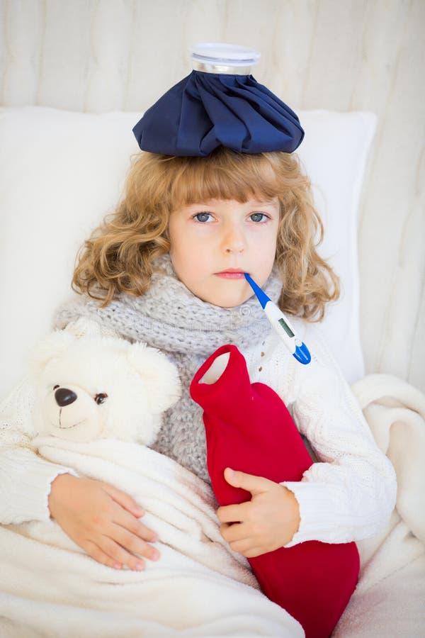 Krankes Kind mit Fieber und Wärmflasche stockfoto