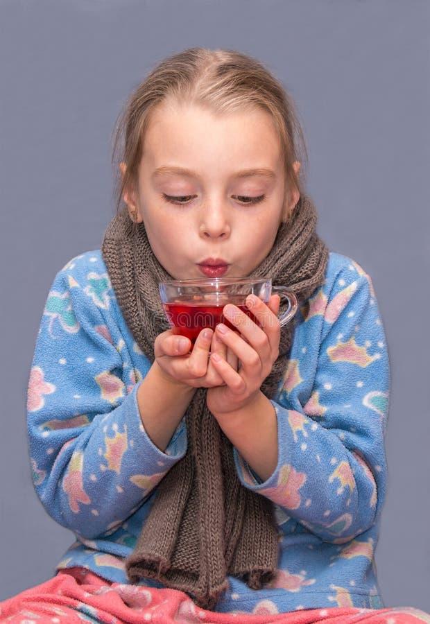 Krankes Kindermädchen trinkt Tee stockfotos