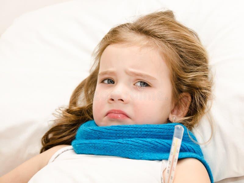Krankes kleines Mädchen, das im Bett liegt stockfoto