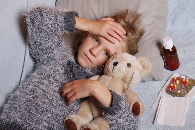 Krankes kleines Mädchen, das im Bett mit ihrem Spielzeug liegt Kinderwintergrippeallergie-Gesundheitswesenkonzept stockfotos