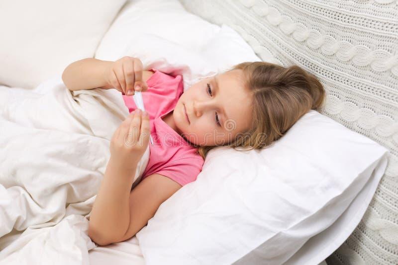 Krankes kleines M?dchen, das im Bett mit Thermometer liegt stockfotografie