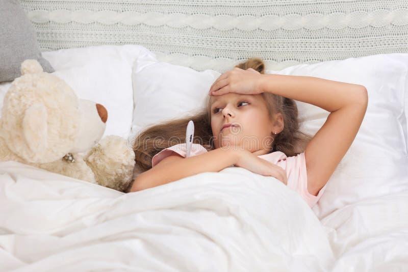 Krankes kleines M?dchen, das im Bett mit Thermometer liegt lizenzfreie stockfotografie